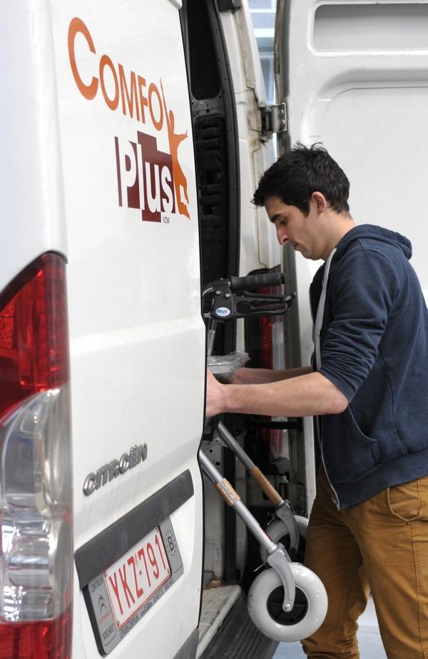 Een medewerker die een Comfoplusbusje vollaadt